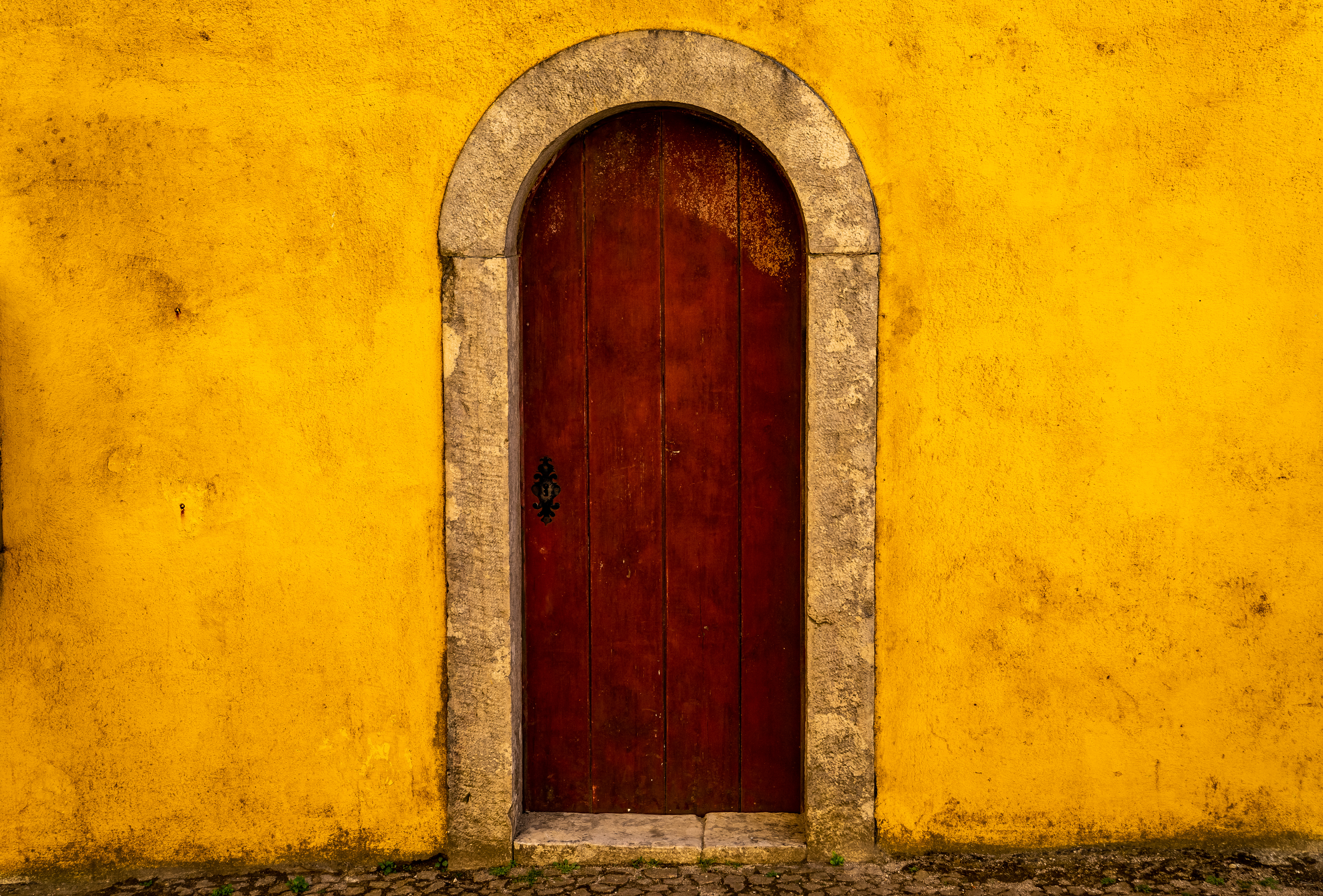 lone red door in a bright yellow stucco wall