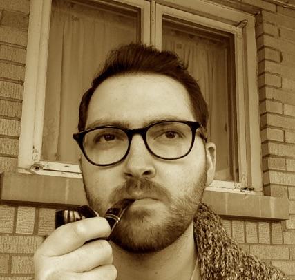 Jake Bailey headshot of man in glasses smoking pipe