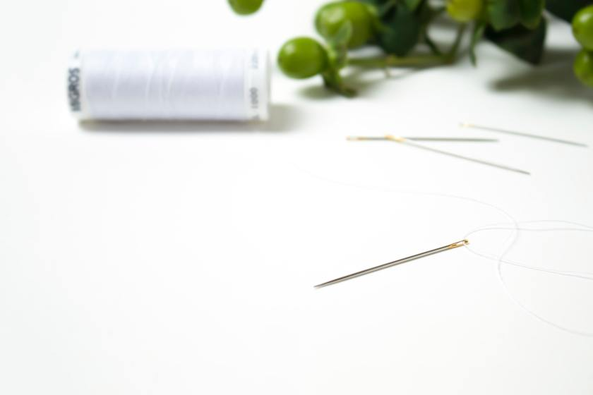photo of a single sewing needle in foreground with spool of white thread in background